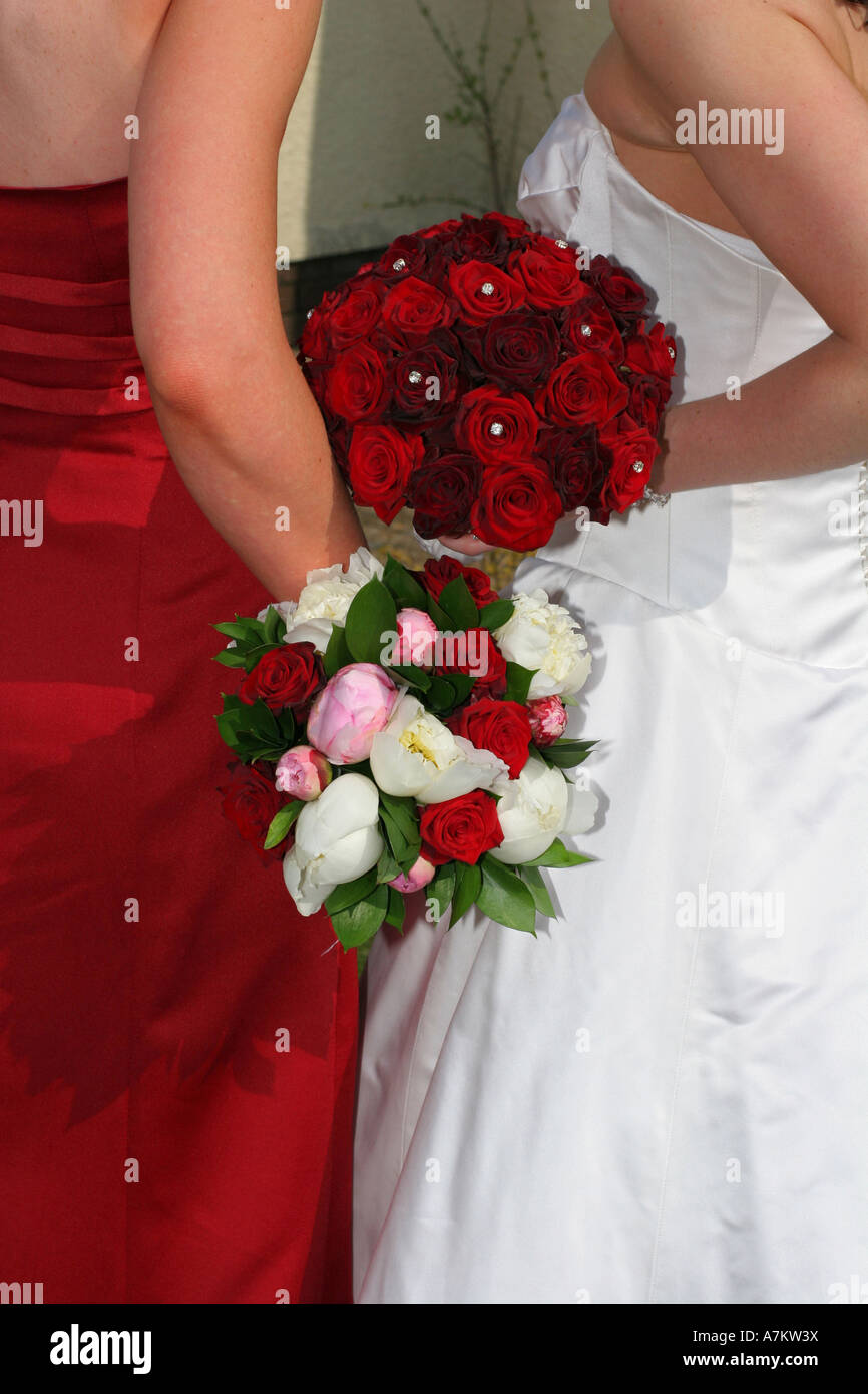 A Bride In White Wedding Dress Holds Red Rose Flower Bouquet On