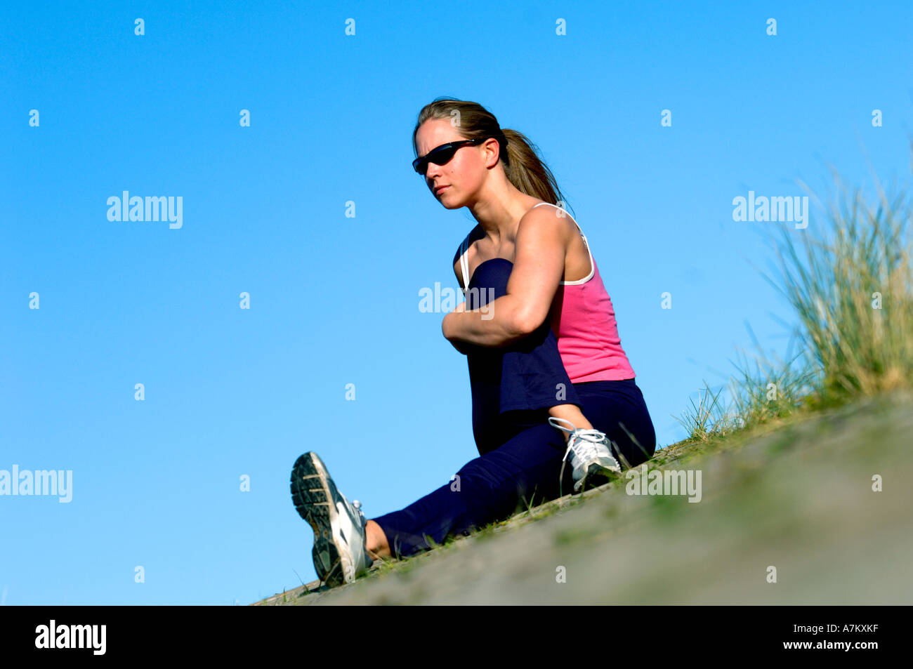 Healthy young woman stretches before workout in sunshine - Stock Image