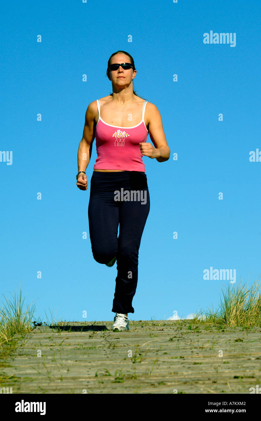 healthy young woman jogging keeping fit - Stock Image