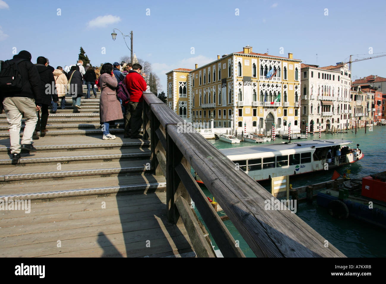 View of tourists climbing the famous Academia bridge with Grand Canal and water bus to the right Venice Italy EU - Stock Image