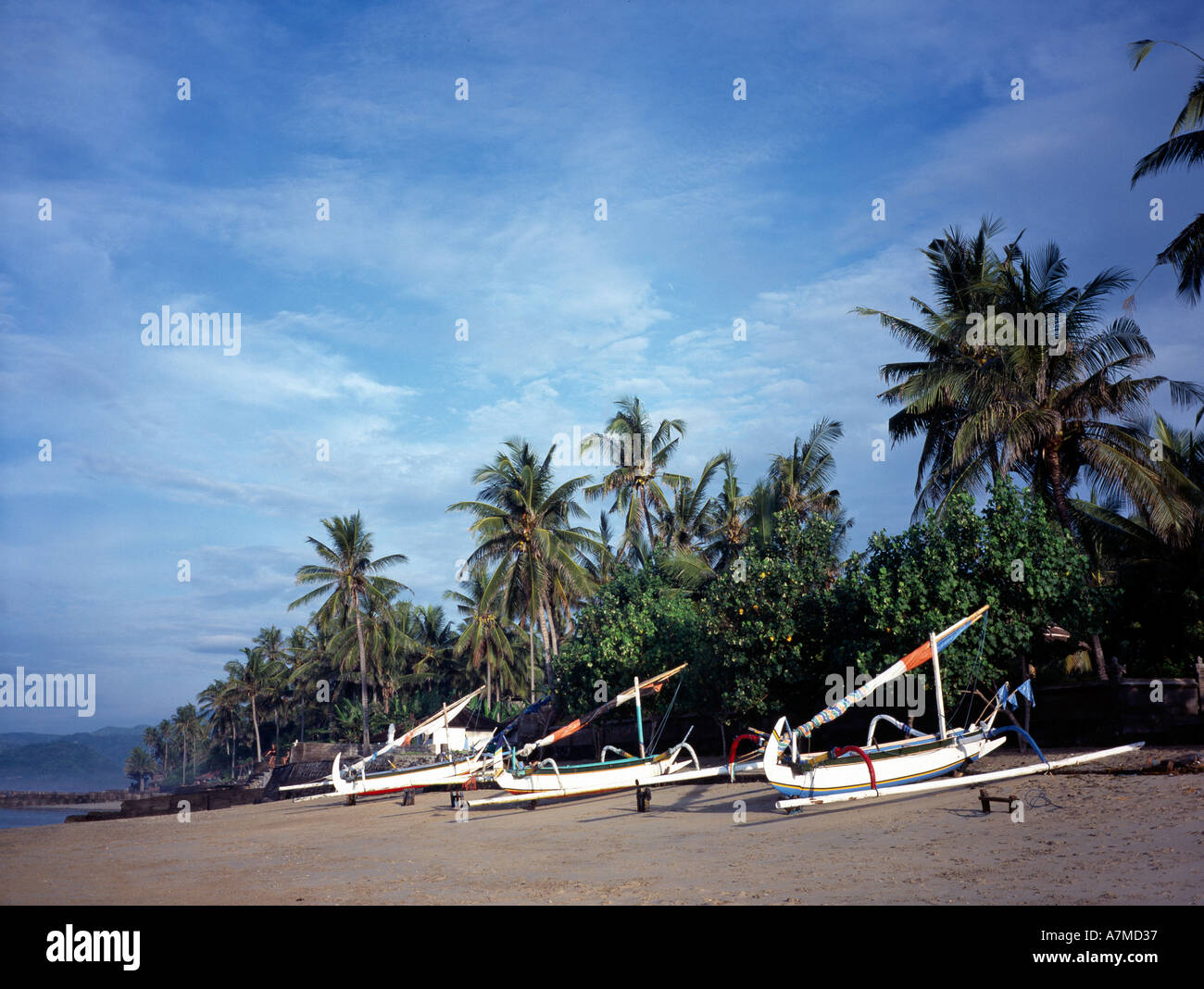 Indonesia Bali Candidasa fishing boats on the beach eroded by mining dead coral for construction - Stock Image
