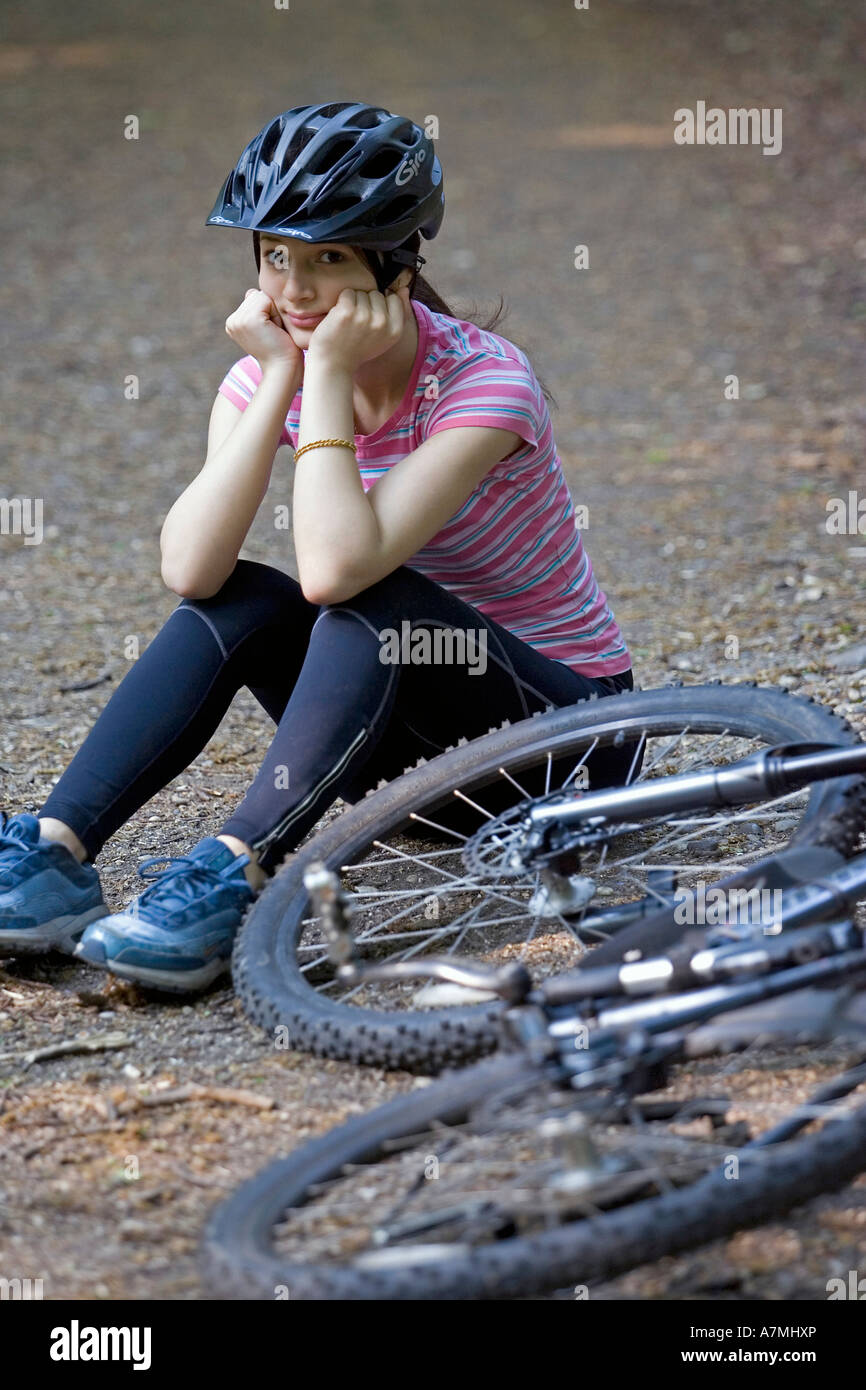 Girl sitting on ground after falling off her mountain bike riding along a forest path - Stock Image