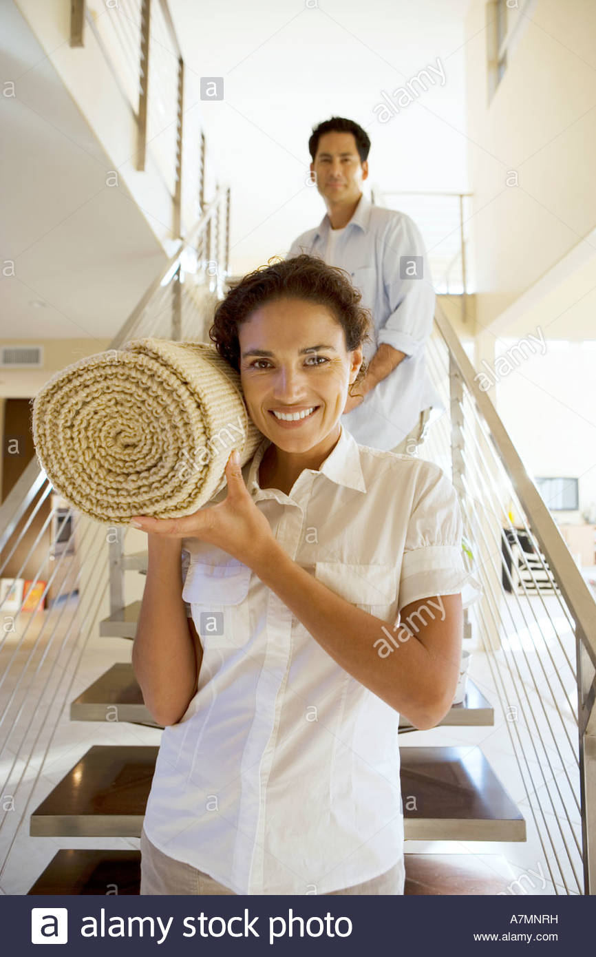 Couple moving house carrying rolled up carpet on shoulders down staircase front view smiling portrait - Stock Image