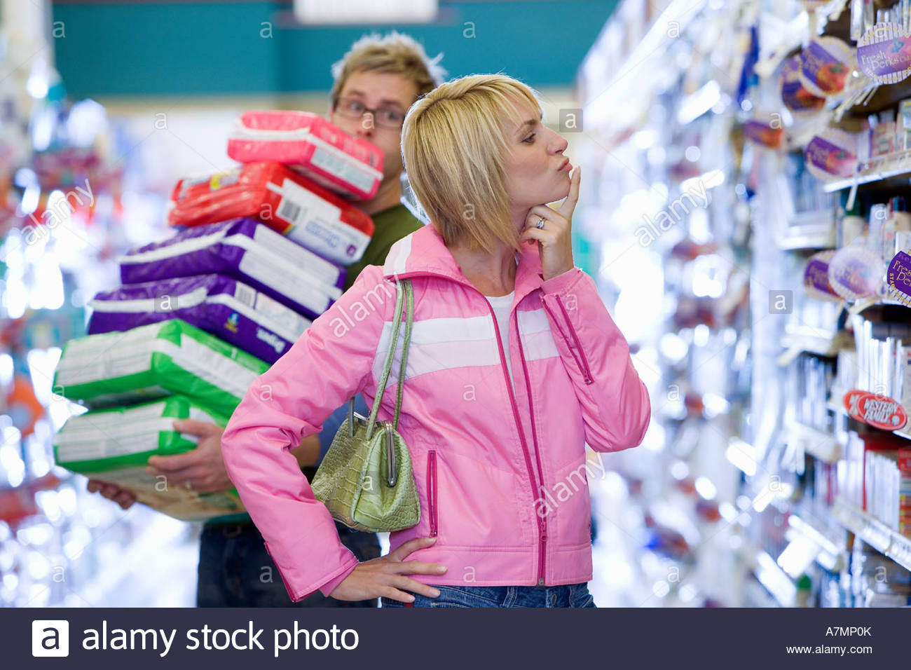 Couple shopping in supermarket man struggling with stack of items woman thinking - Stock Image