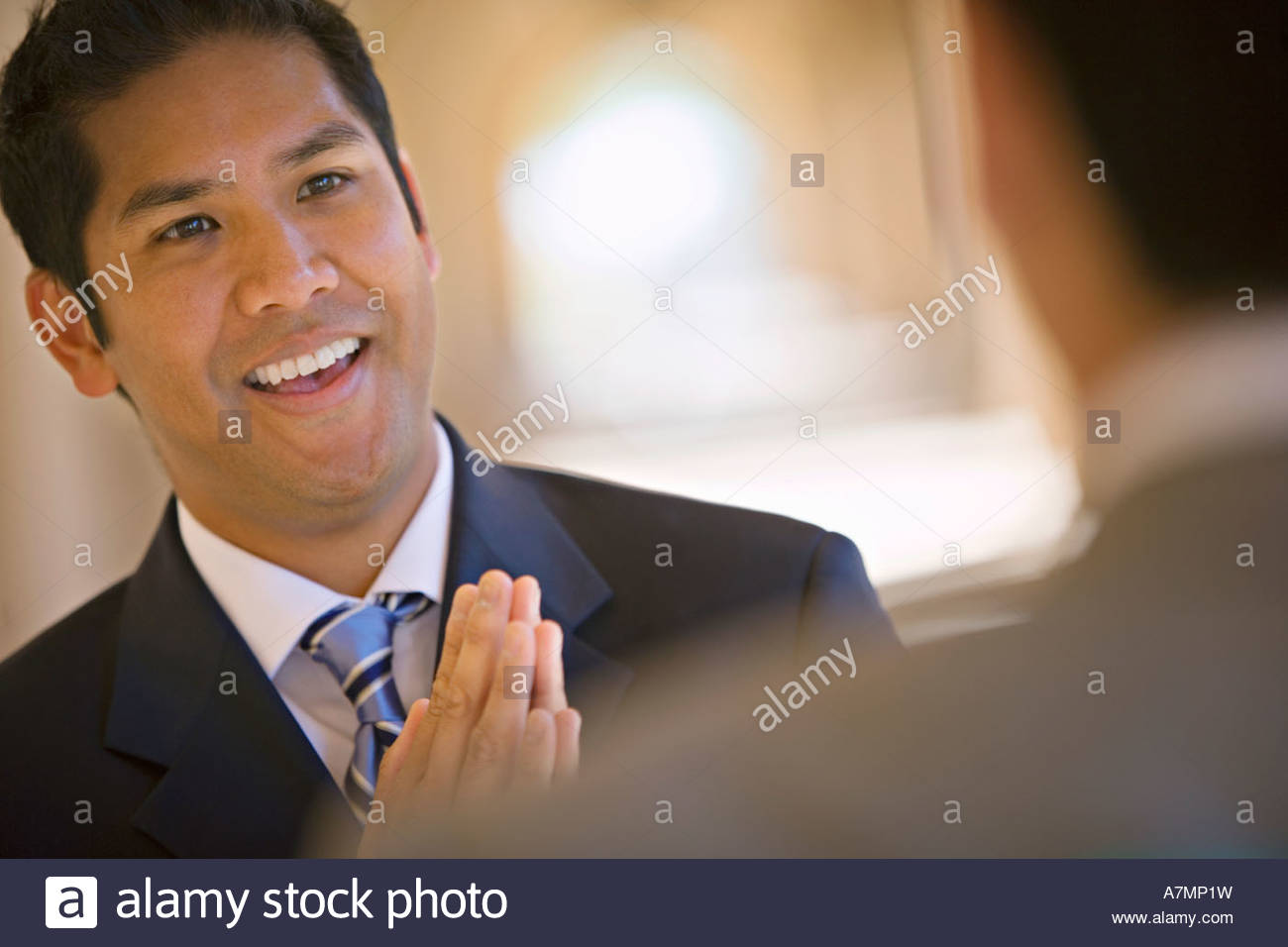 Respectful businessman greeting counterpart in building arcade smiling differential focus tilt - Stock Image