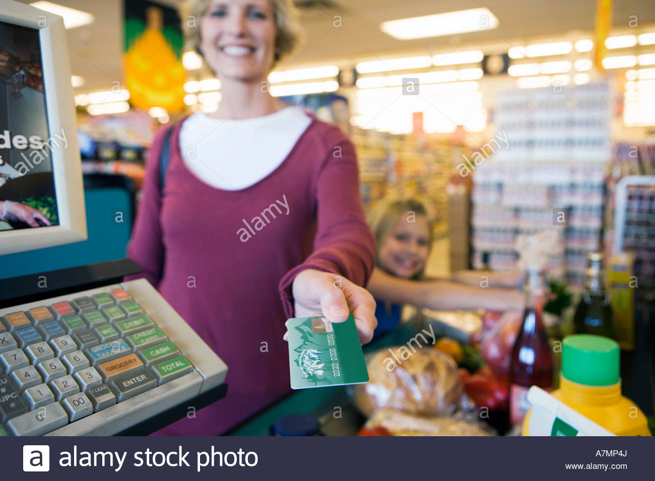 Girl 7 9 placing items on checkout conveyor belt in supermarket mother paying with credit card smiling - Stock Image