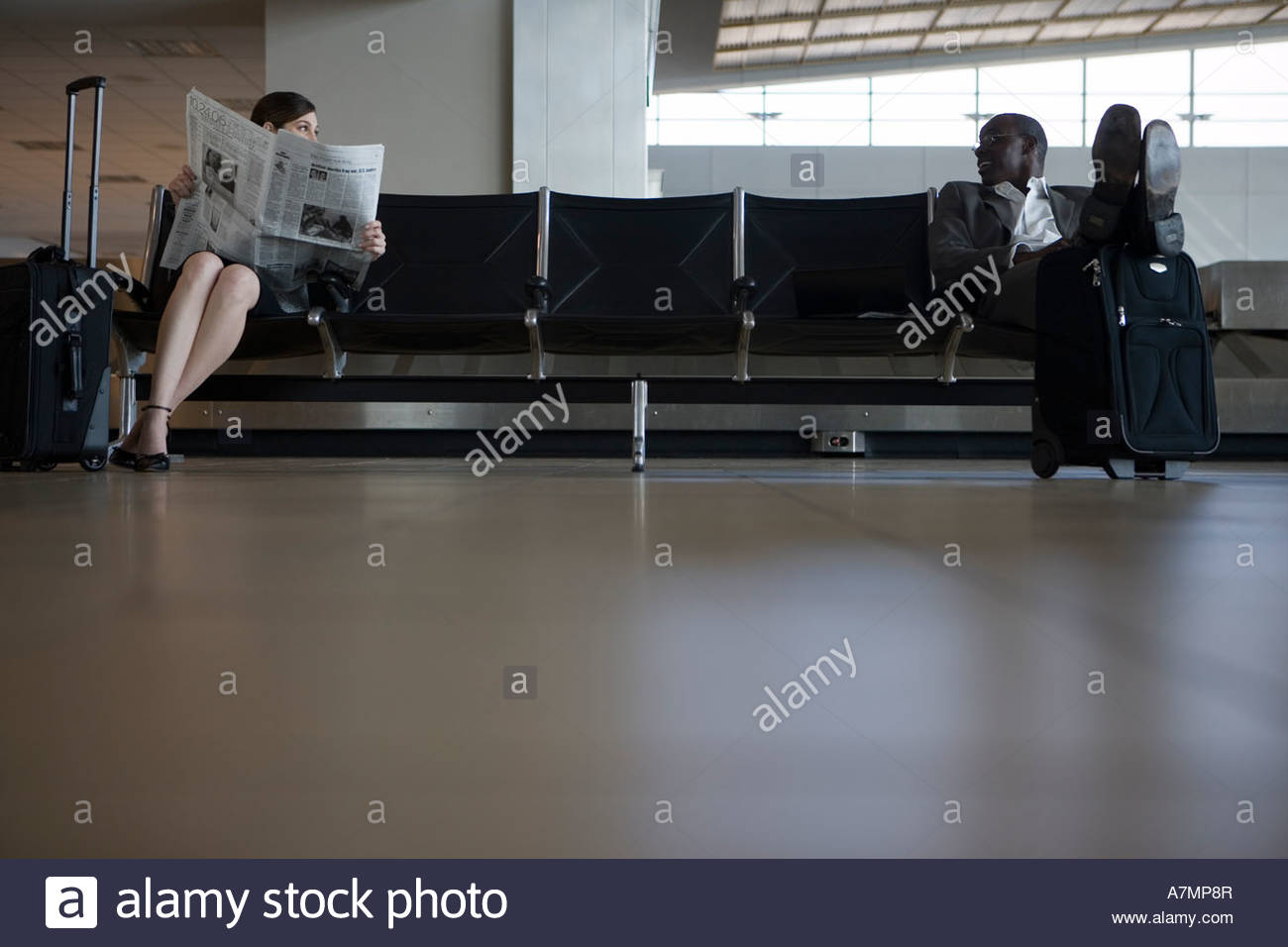 Businesswoman and businessman waiting in airport departure lounge woman reading newspaper - Stock Image