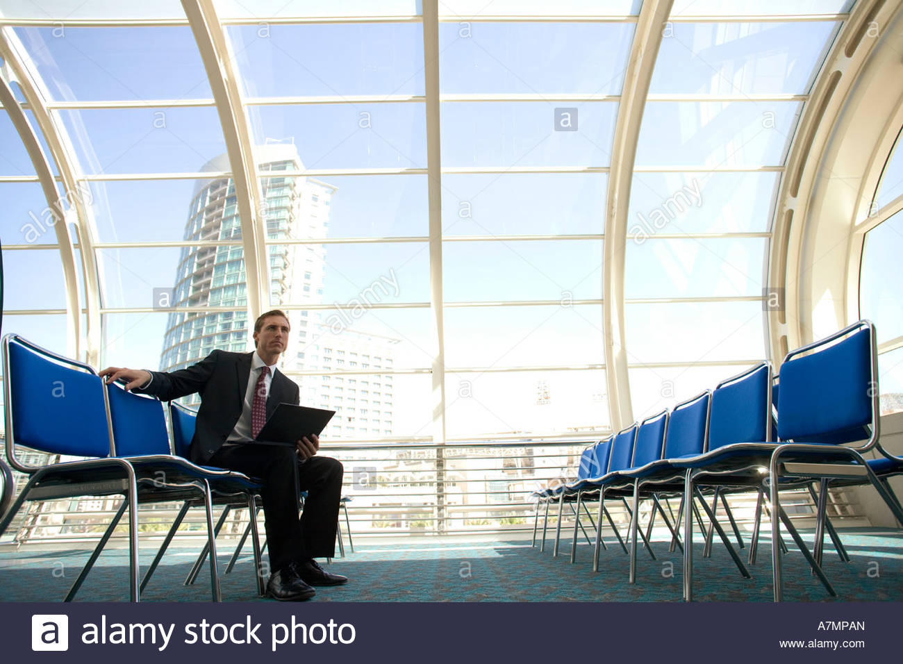 Businessman waiting in airport departure lounge using laptop side view - Stock Image