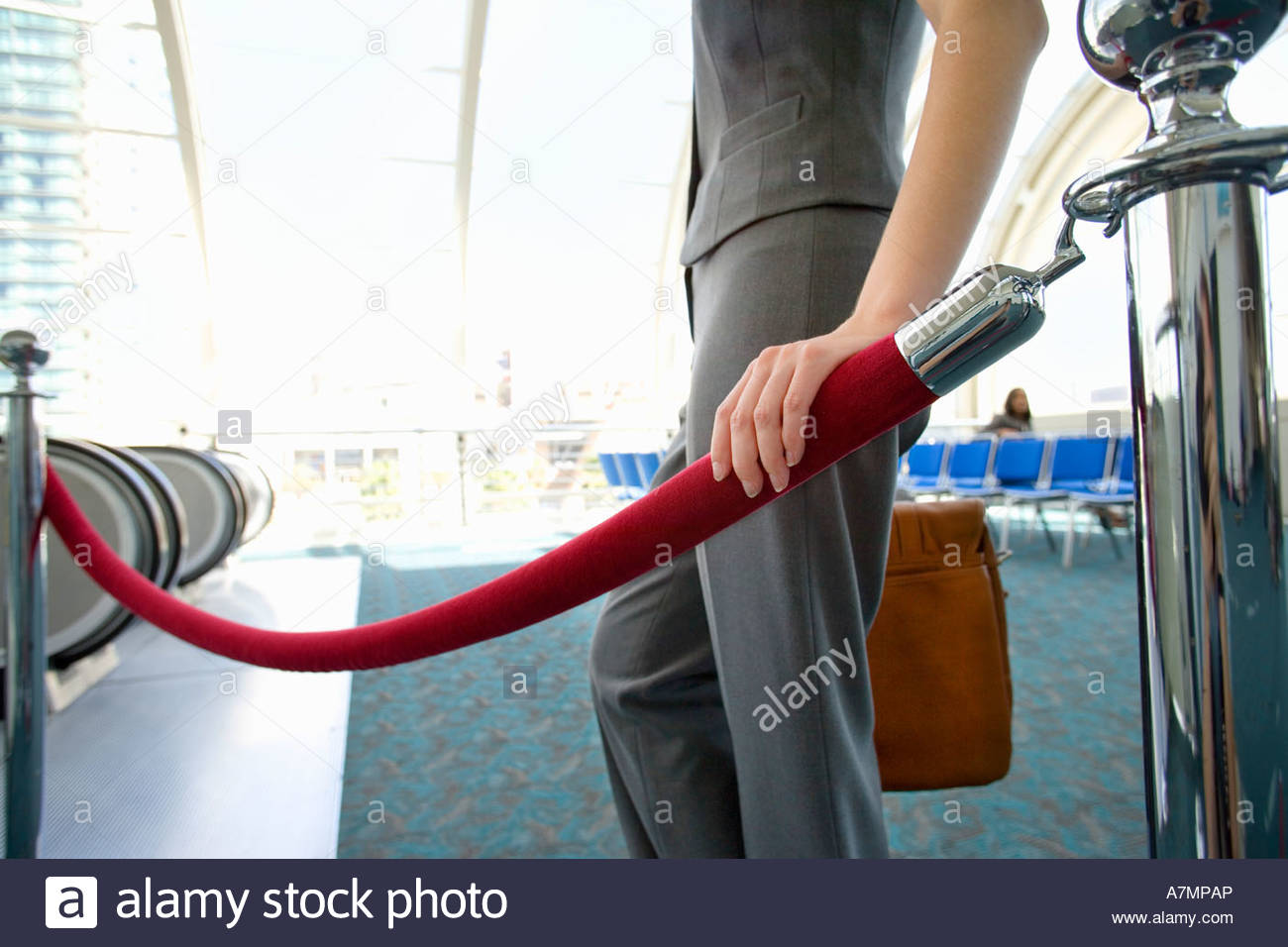 Businesswoman standing beside rope barrier near escalators in airport departure lounge mid section - Stock Image