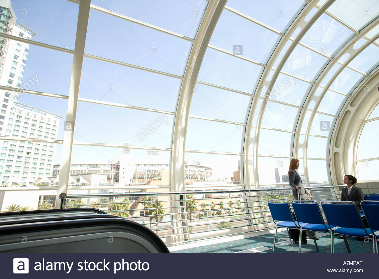 Two businesswomen waiting in airport departure lounge near escalator side view - Stock Image