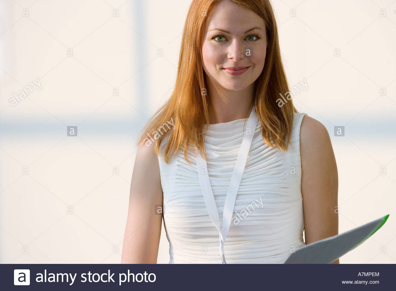 Woman in white sleeveless top holding folder smiling front view portrait - Stock Image