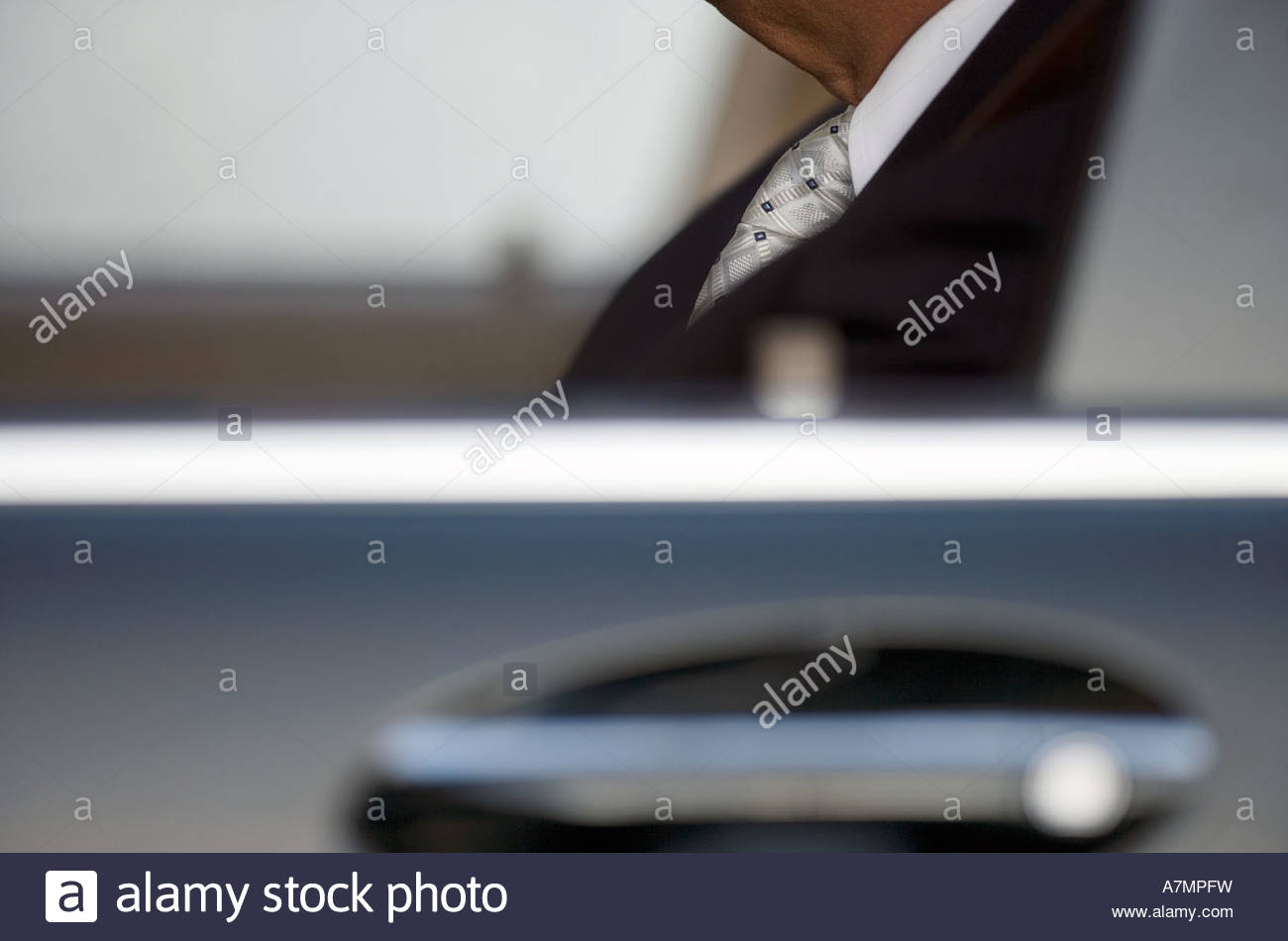 Businessman sitting in car view through window side view close up differential focus - Stock Image