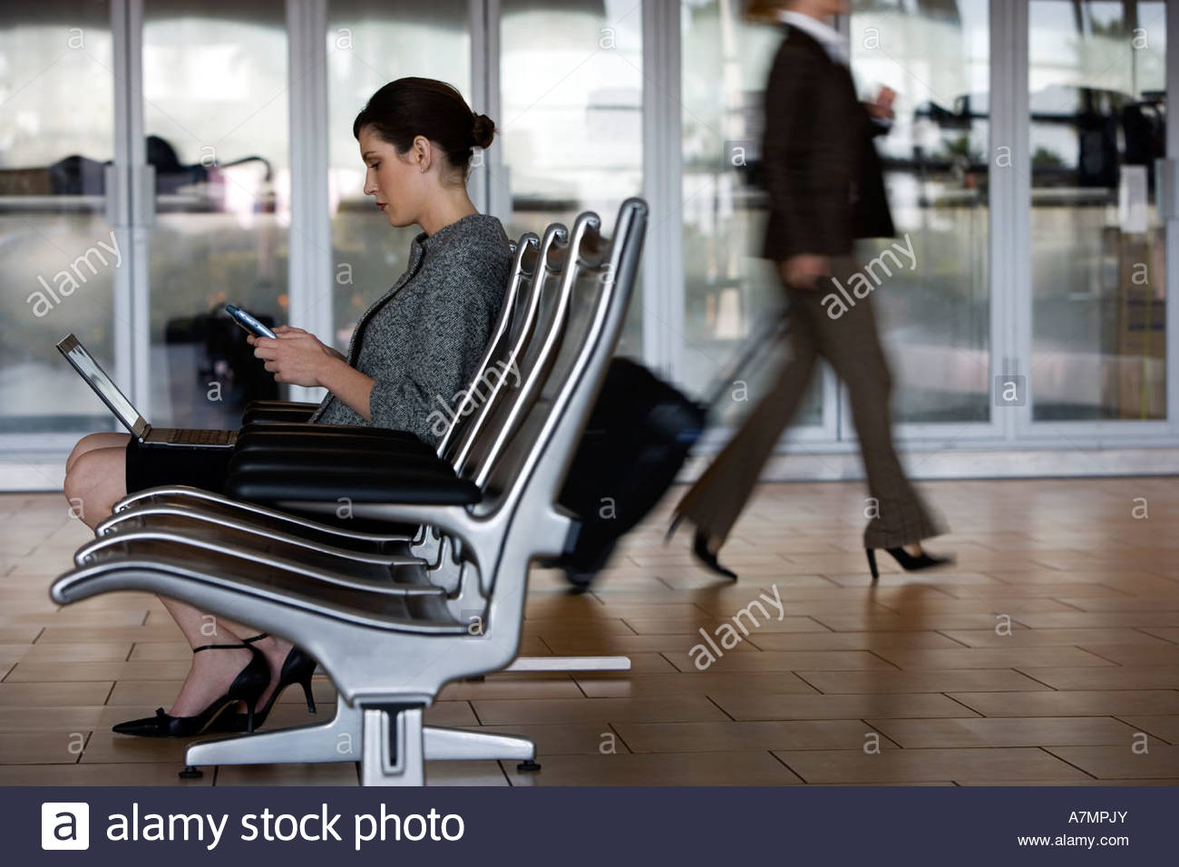Businesswoman sitting in waiting area using laptop and electronic organiser profile Stock Photo
