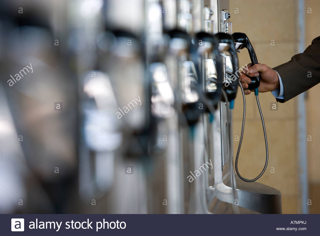 Businessman using public payphone side view focus on background - Stock Image