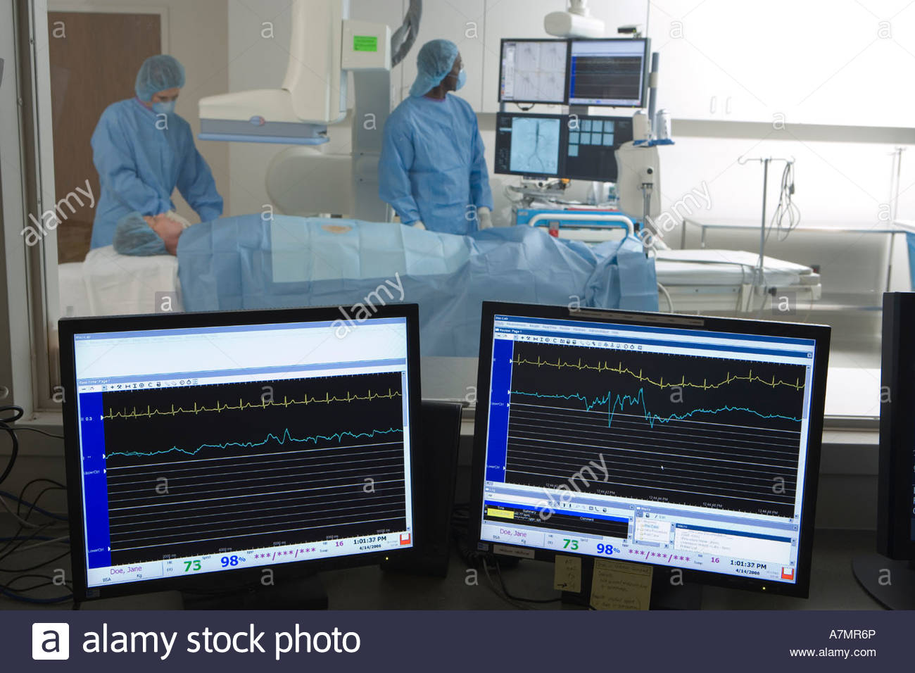Doctors scanning patient in hospital visual monitors in foreground - Stock Image