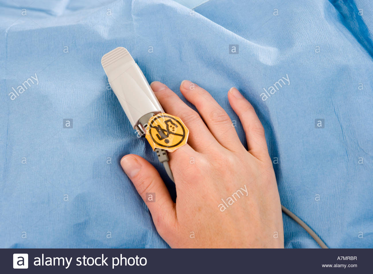 Patient wearing pulse oxymeter on finger close up overhead view - Stock Image
