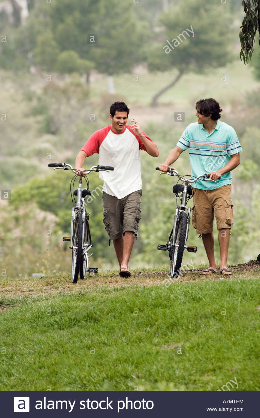 Two teenage boys 17 19 walking side by side with bicycles talking smiling front view - Stock Image