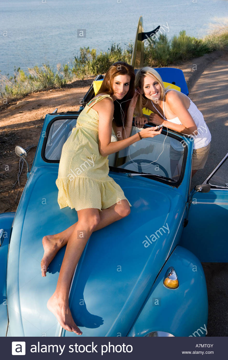 Teenage girls 17 19 listening to MP3 player on car bonnet sharing headphones elevated view Stock Photo