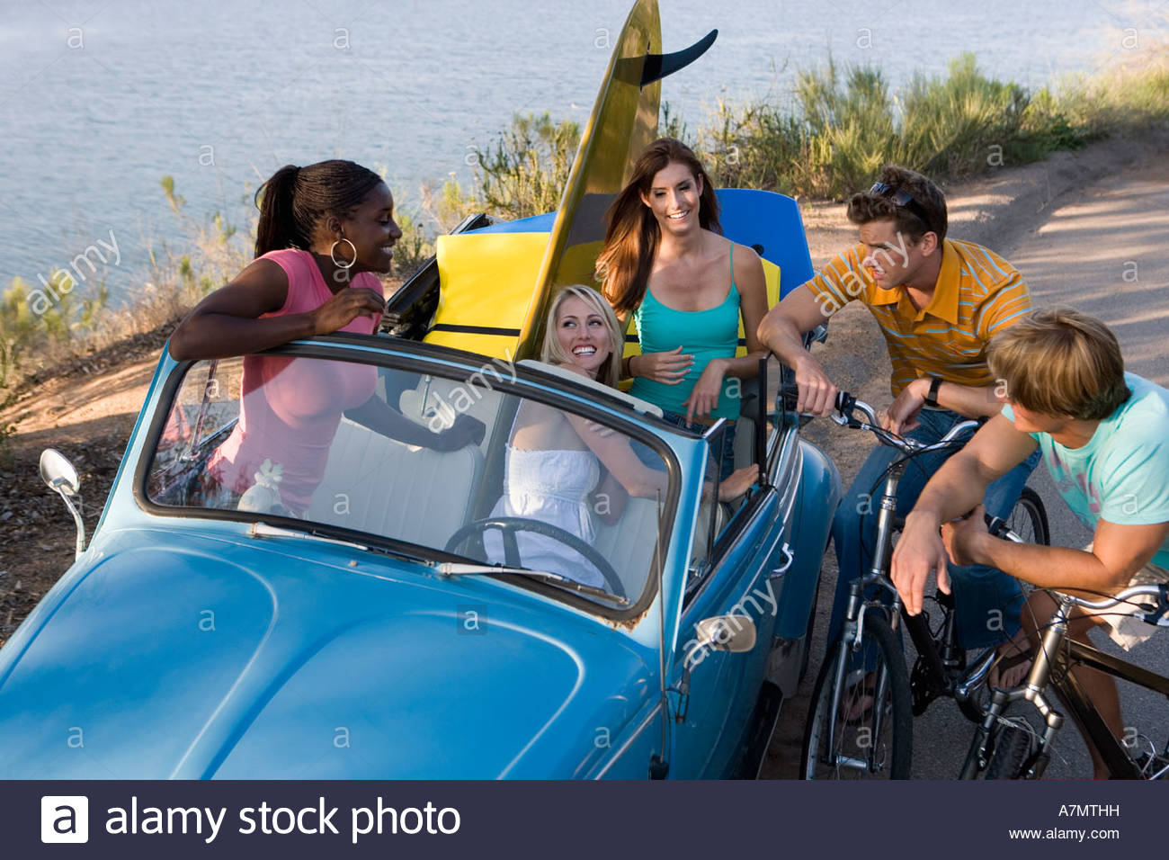 Teenagers (17-19) talking by roadside, girls in blue convertible car, boys on bicycles, elevated view Stock Photo