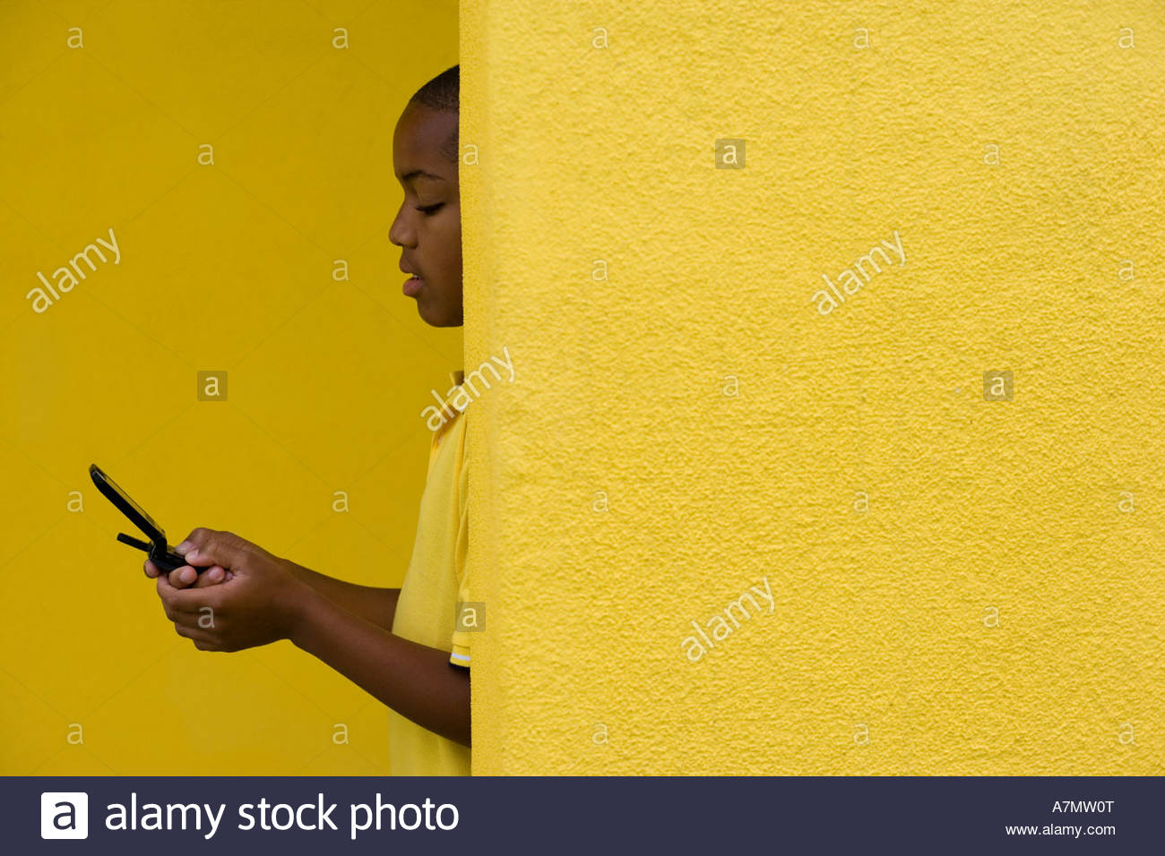 Boy 9 11 standing behind yellow wall text messaging on mobile phone profile - Stock Image