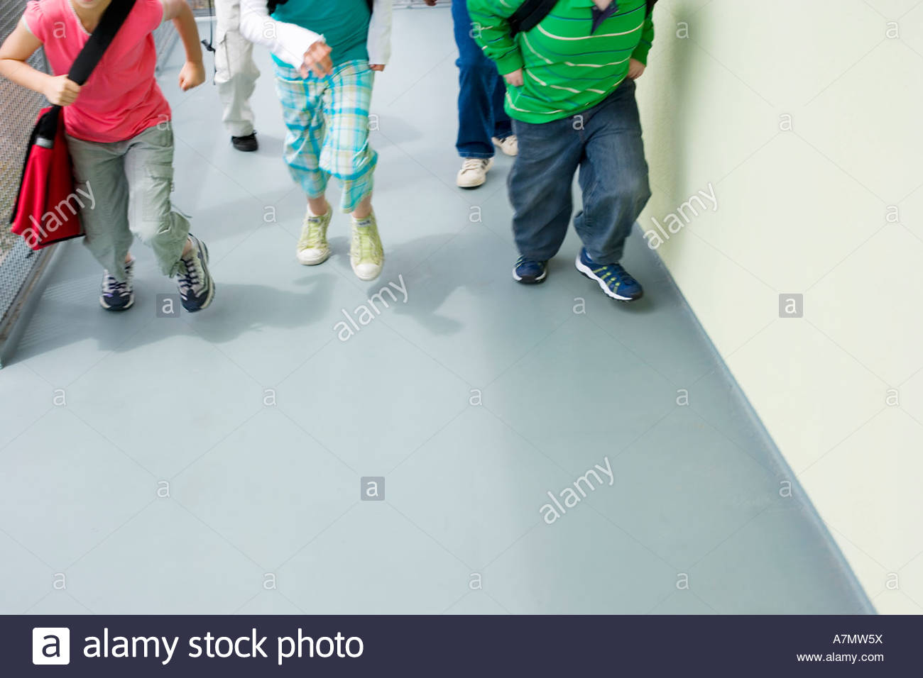 Children 10 12 running in school corridor front view low section - Stock Image