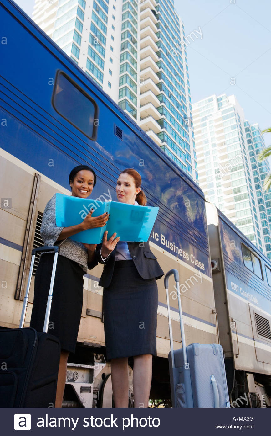 Two businesswomen discussing document on railway platform beside stationary passenger train low angle view - Stock Image