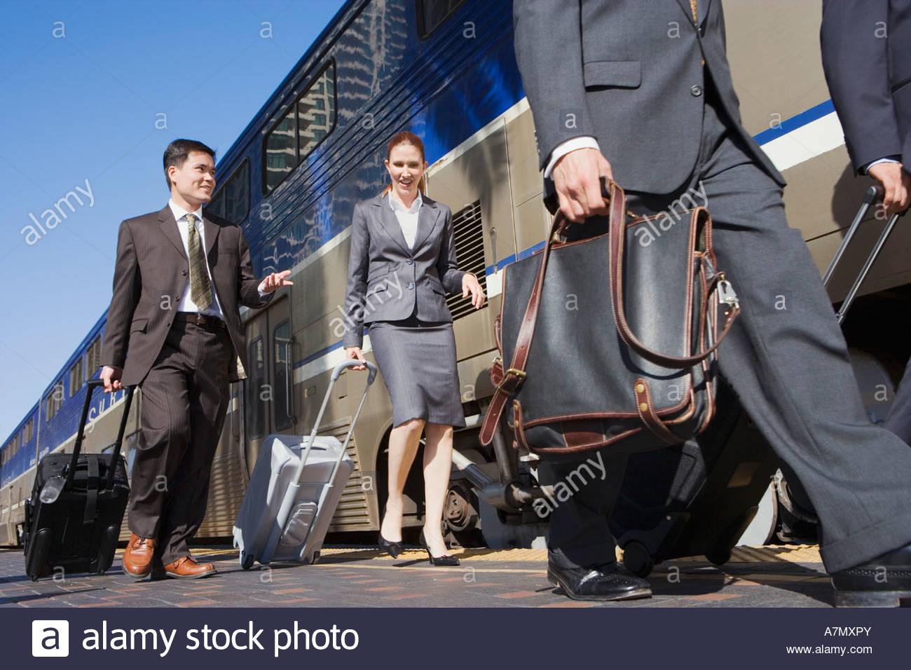 Four business people walking along railway platform beside stationary passenger train surface level - Stock Image