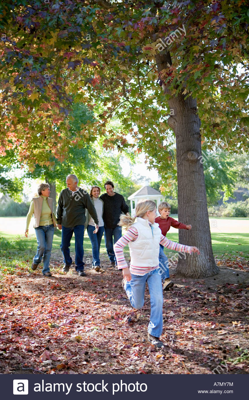 Multi generational family walking beside tree in park in autumn two children 6 9 running on ahead - Stock Image