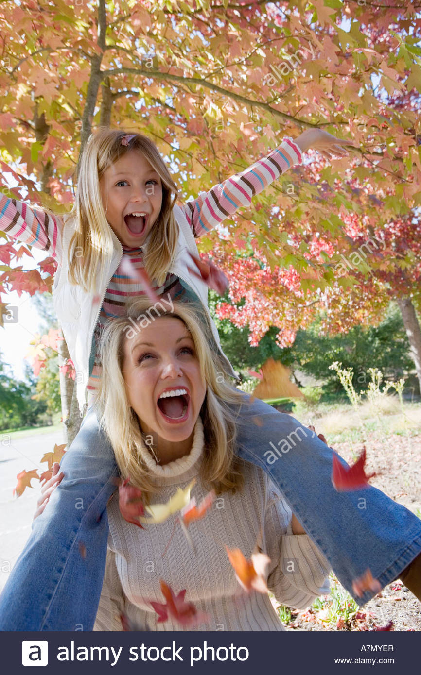 Mother carrying daughter 7 9 on shoulders in park in autumn girl pulling branch laughing - Stock Image