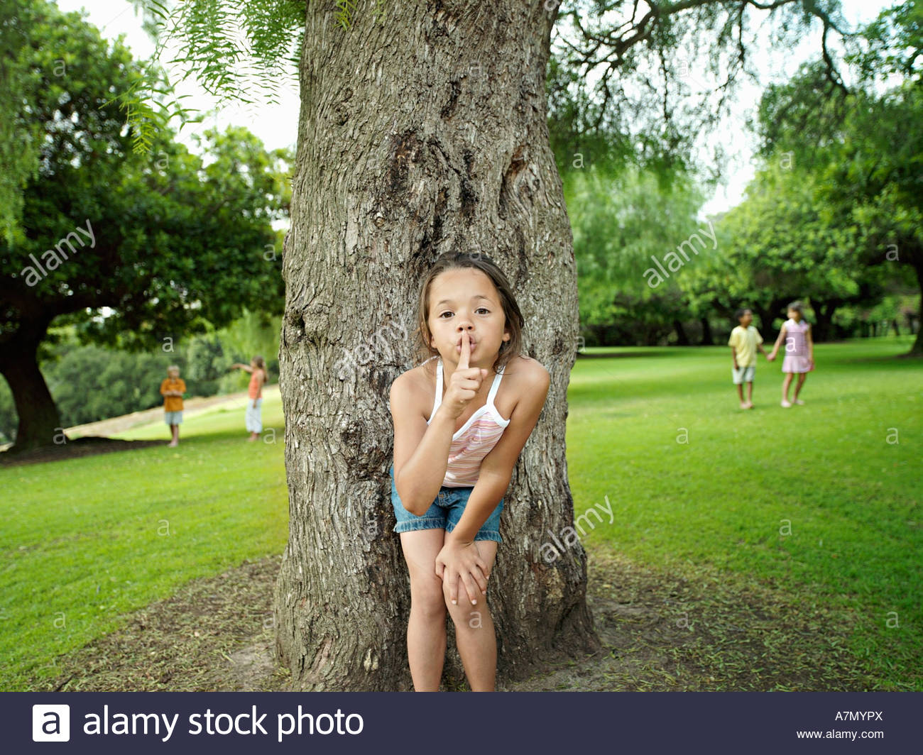 Girl 7 9 with finger on lips playing hide and seek in park hiding from friends behind tree - Stock Image