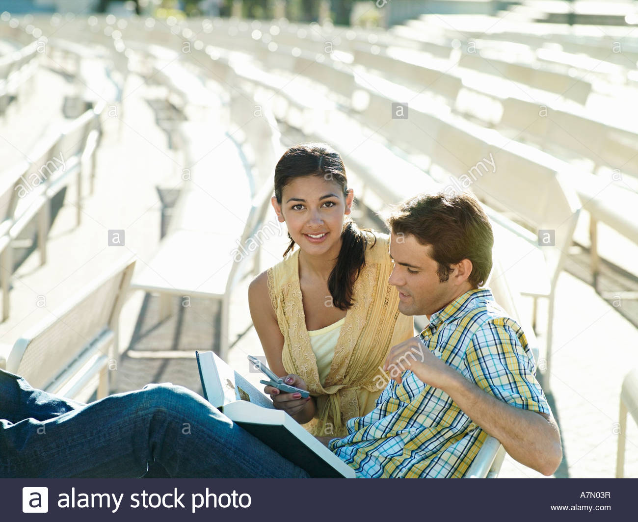 Young couple sitting in outdoor theatre woman holding mobile phone smiling man reading book - Stock Image