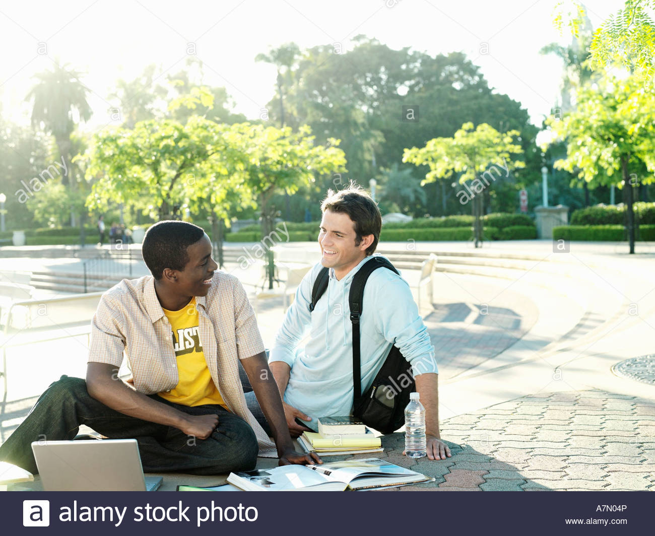 Two male university students sitting on ground with textbooks and laptop smiling - Stock Image