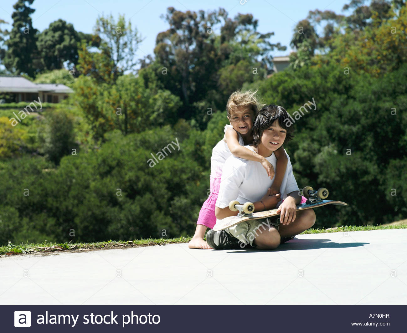 Girl 6 8 embracing brother in park boy 10 12 sitting with skateboard smiling portrait - Stock Image