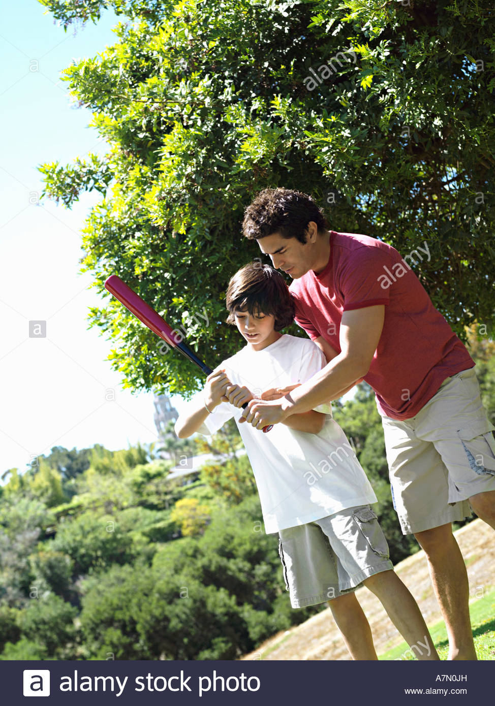 Father teaching son 10 12 how to hold baseball bat standing on grass in park tilt - Stock Image