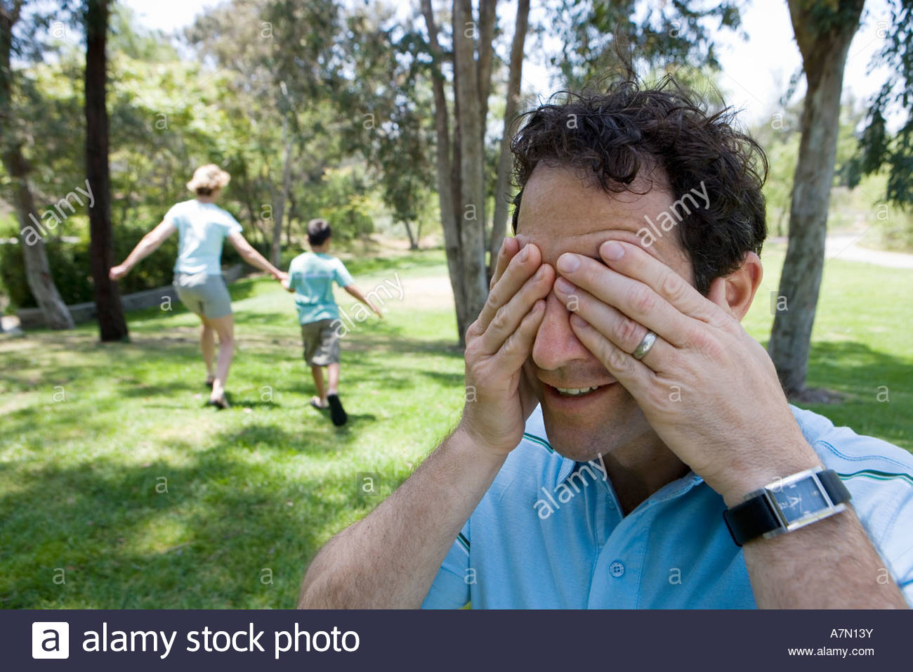 Family playing hide and seek in park boy 9 11 and mother running man covering eyes in foreground Stock Photo
