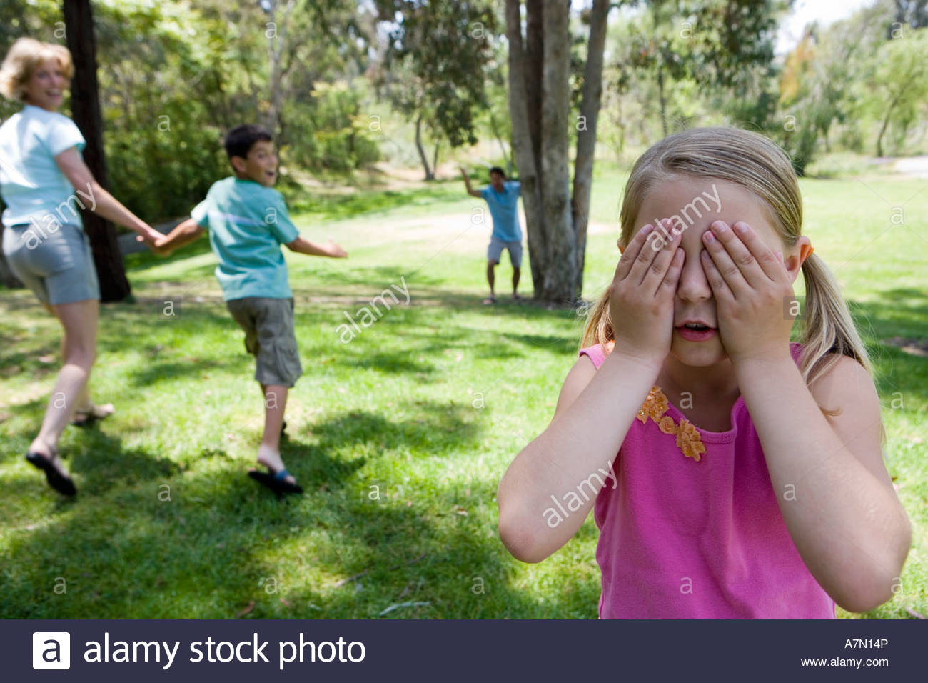 Family playing hide and seek in park focus on girl 8 10 covering eyes in foreground - Stock Image