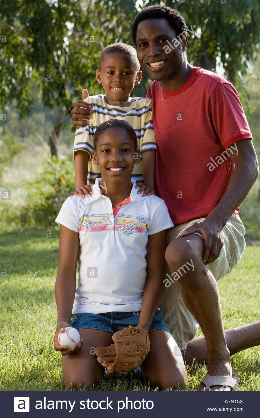 Father kneeling with two children 6 13 on grass in park smiling portrait - Stock Image