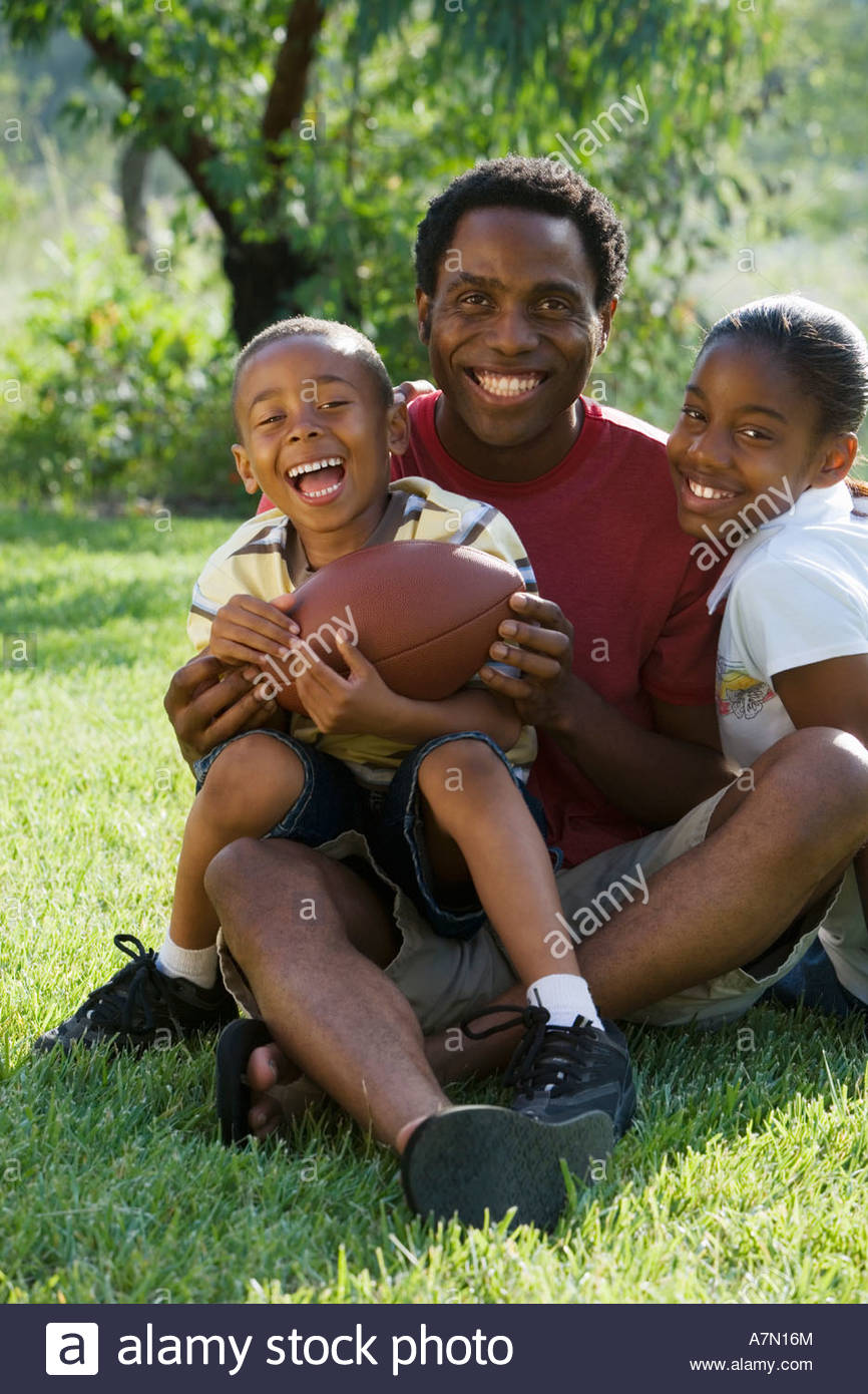 Father sitting with two children 6 13 in park holding american football smiling portrait - Stock Image