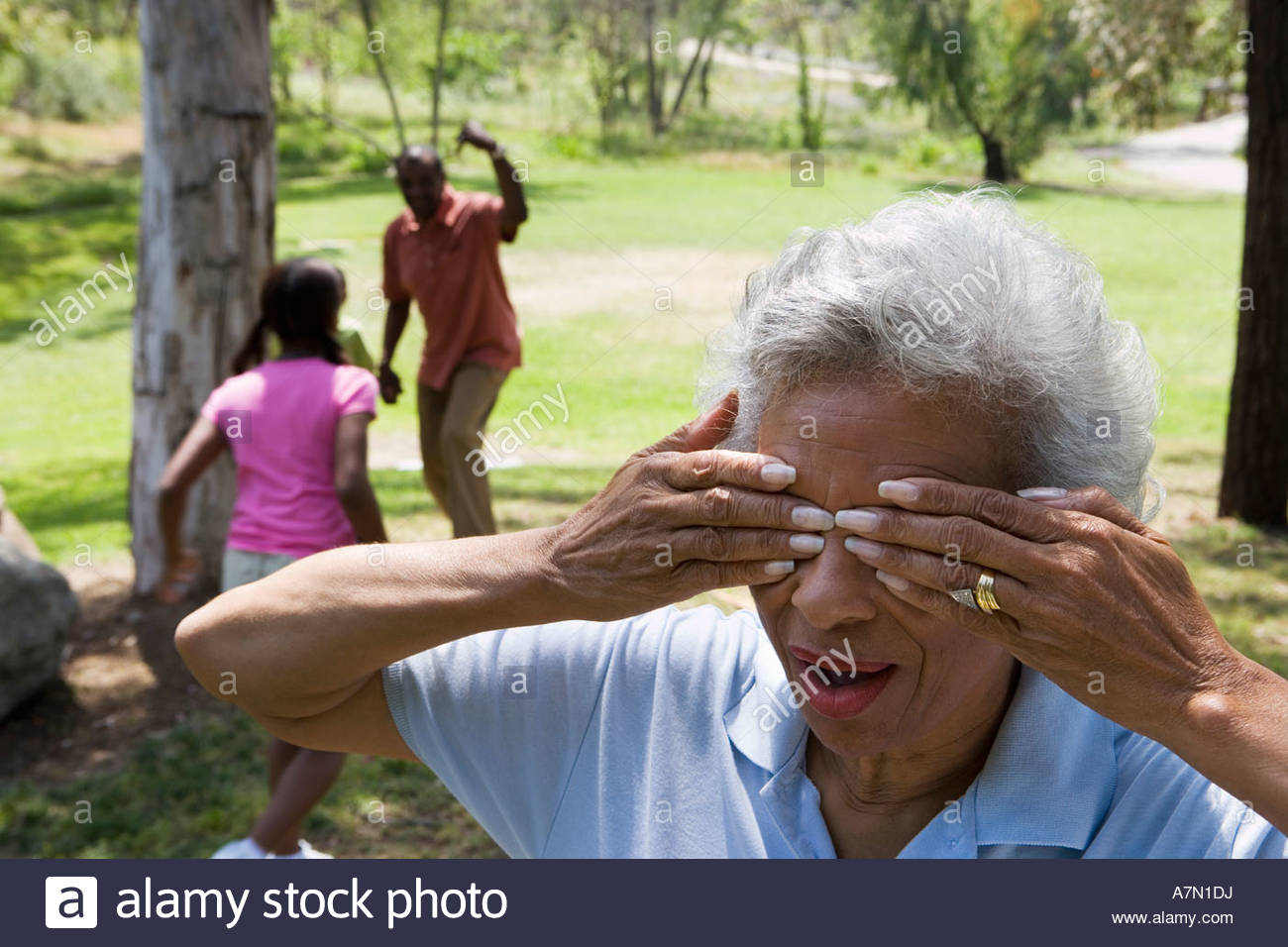 Children 6 10 playing hide and seek with grandparents in park senior woman covering eyes - Stock Image