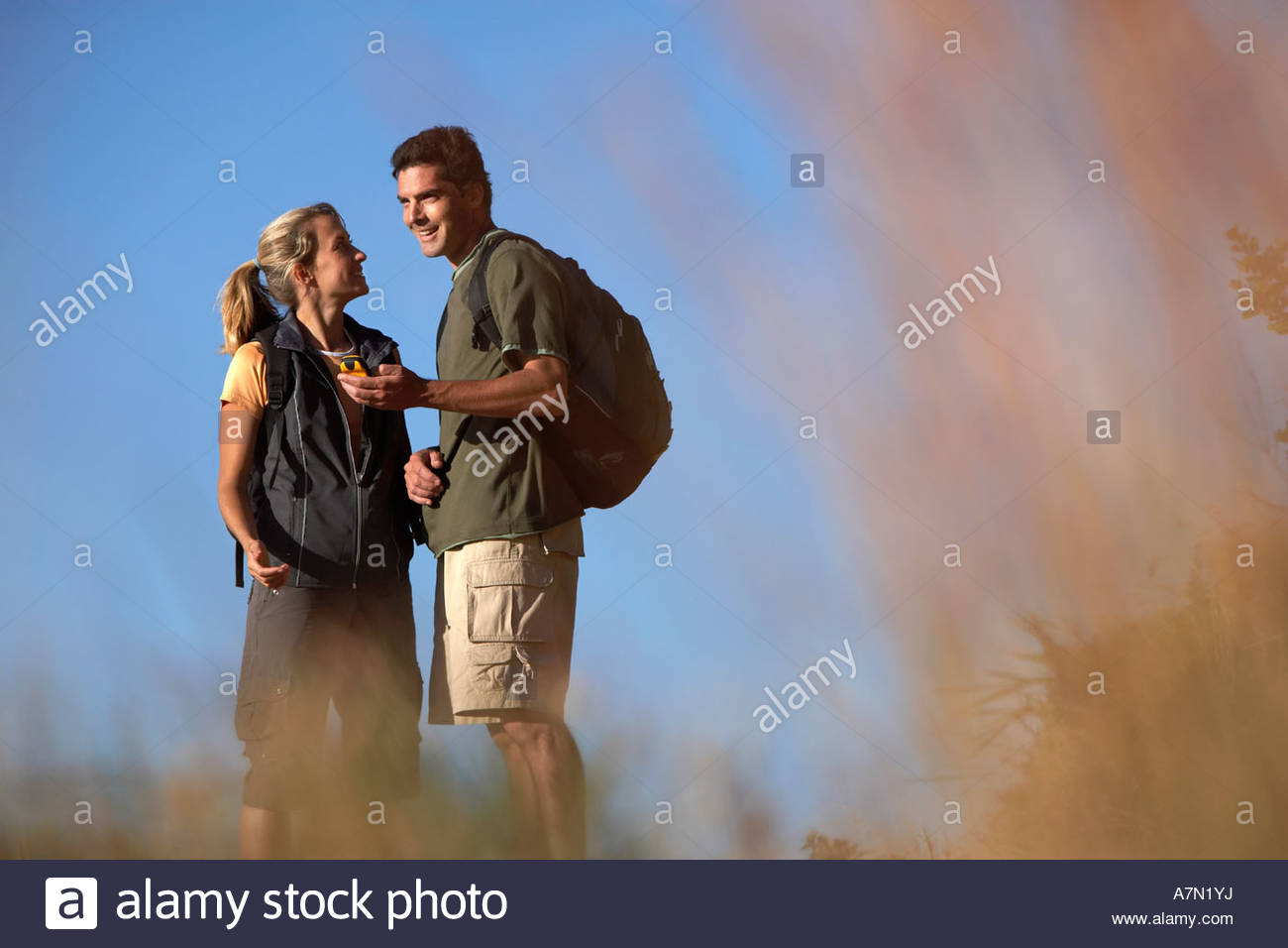 Couple hiking man holding navigation system smiling focus on background - Stock Image