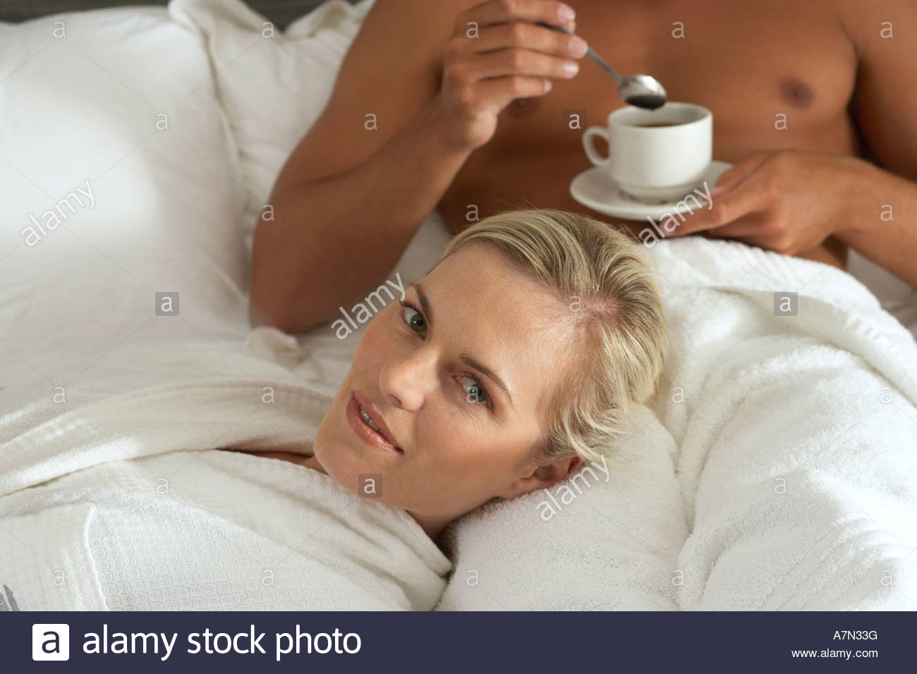 Couple in bathrobes relaxing on hotel bed woman with head on man s lap man drinking coffee - Stock Image
