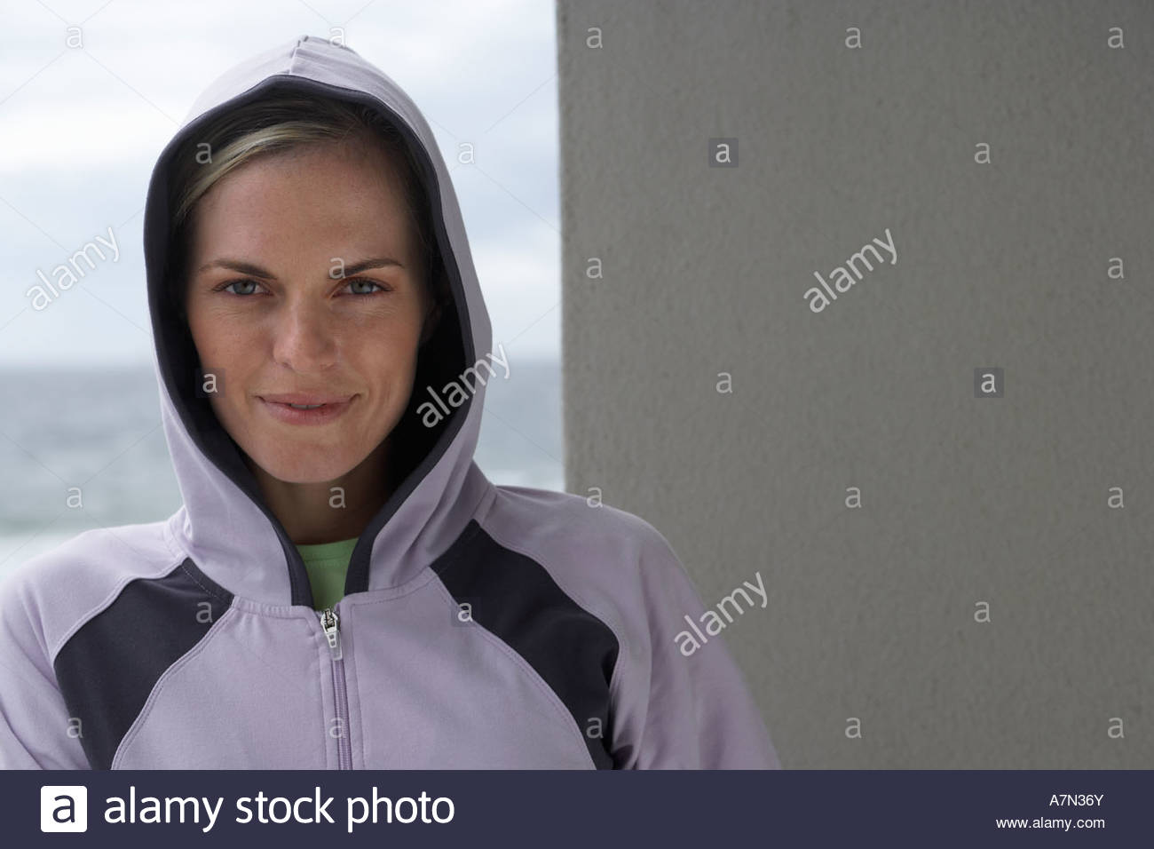 Woman wearing hooded top standing on balcony with ocean view smiling front view portrait - Stock Image