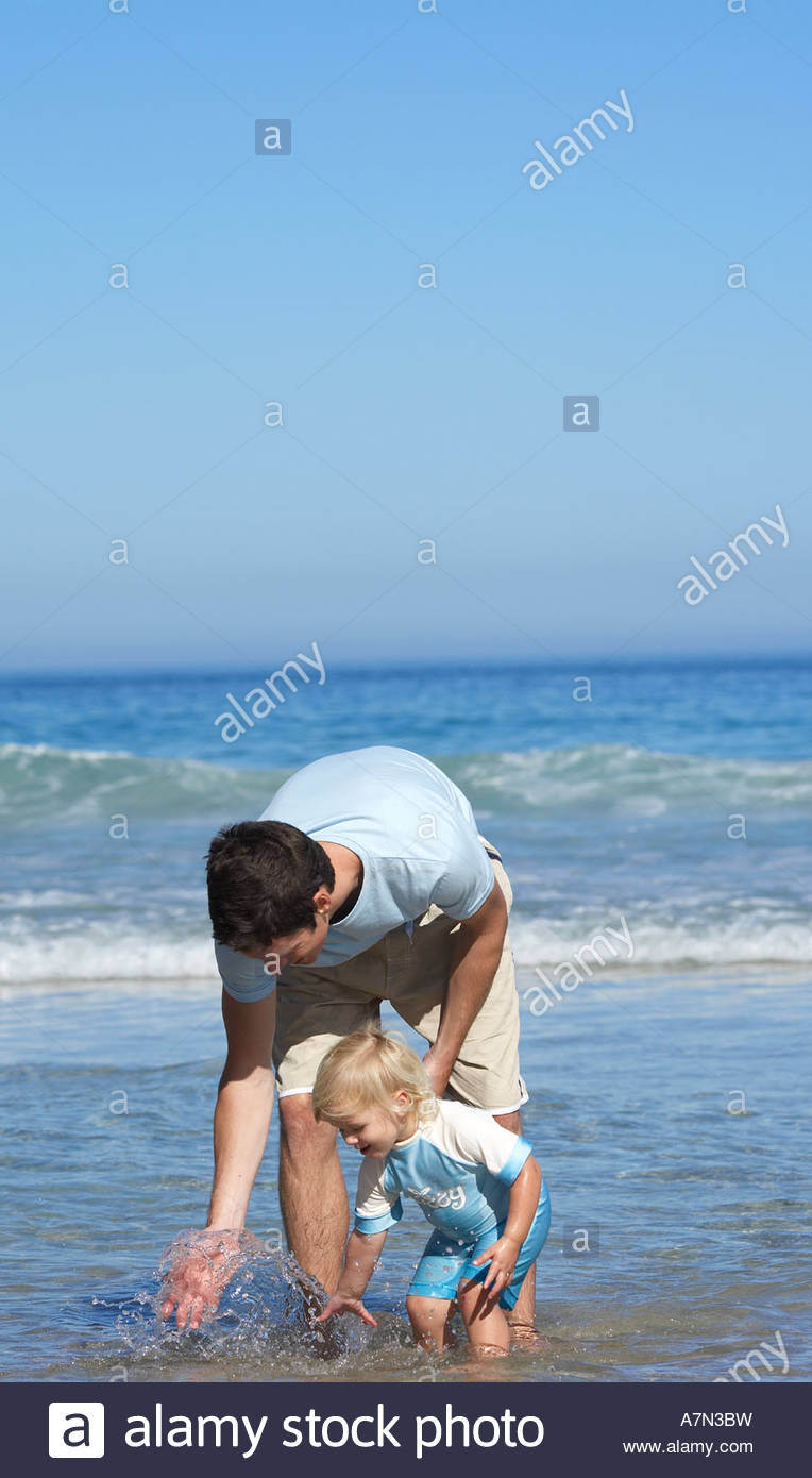 Father and daughter 2 4 looking for shells on beach standing ankle deep in water side view - Stock Image
