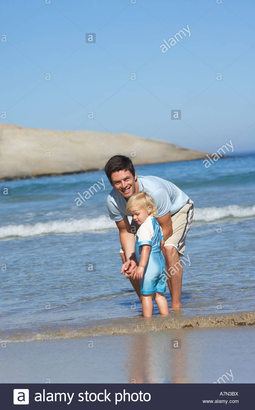 Father and daughter 2 4 standing ankle deep in water on beach side view smiling portrait tilt - Stock Image