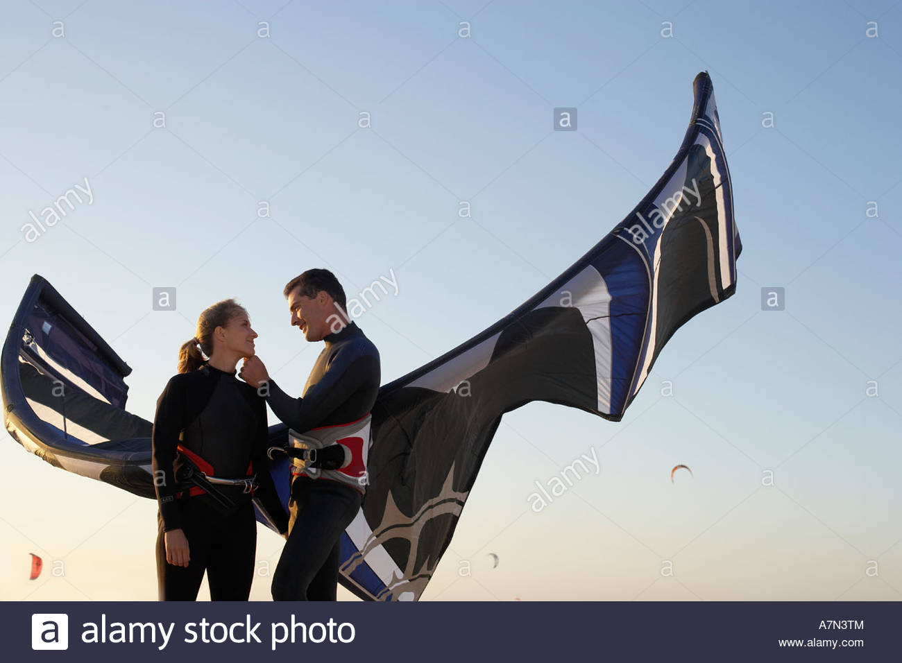 Young couple in wetsuits standing on beach with kiteboard at sunset smiling low angle view - Stock Image