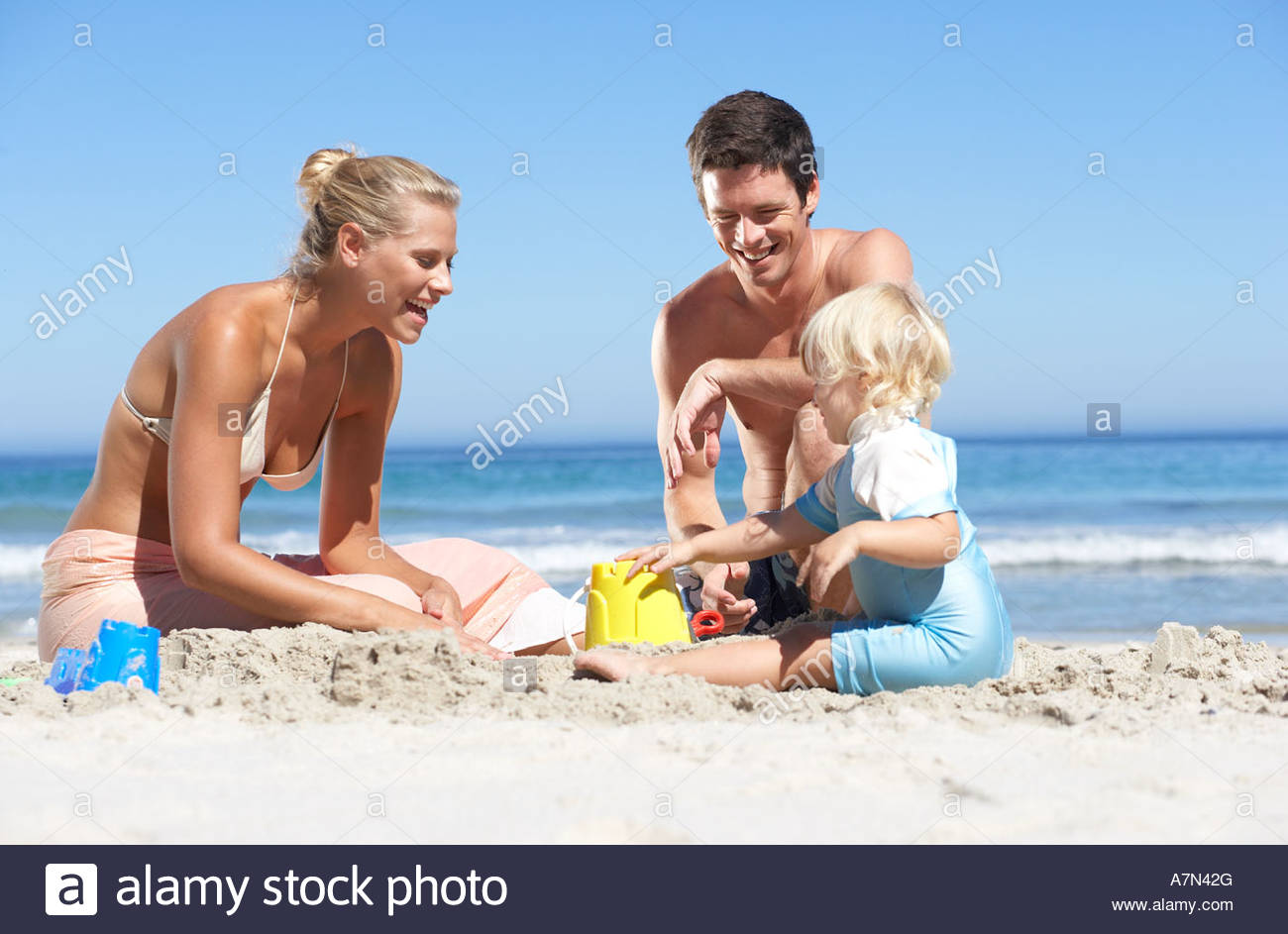 Two generation family building sandcastles on sandy beach smiling Stock Photo