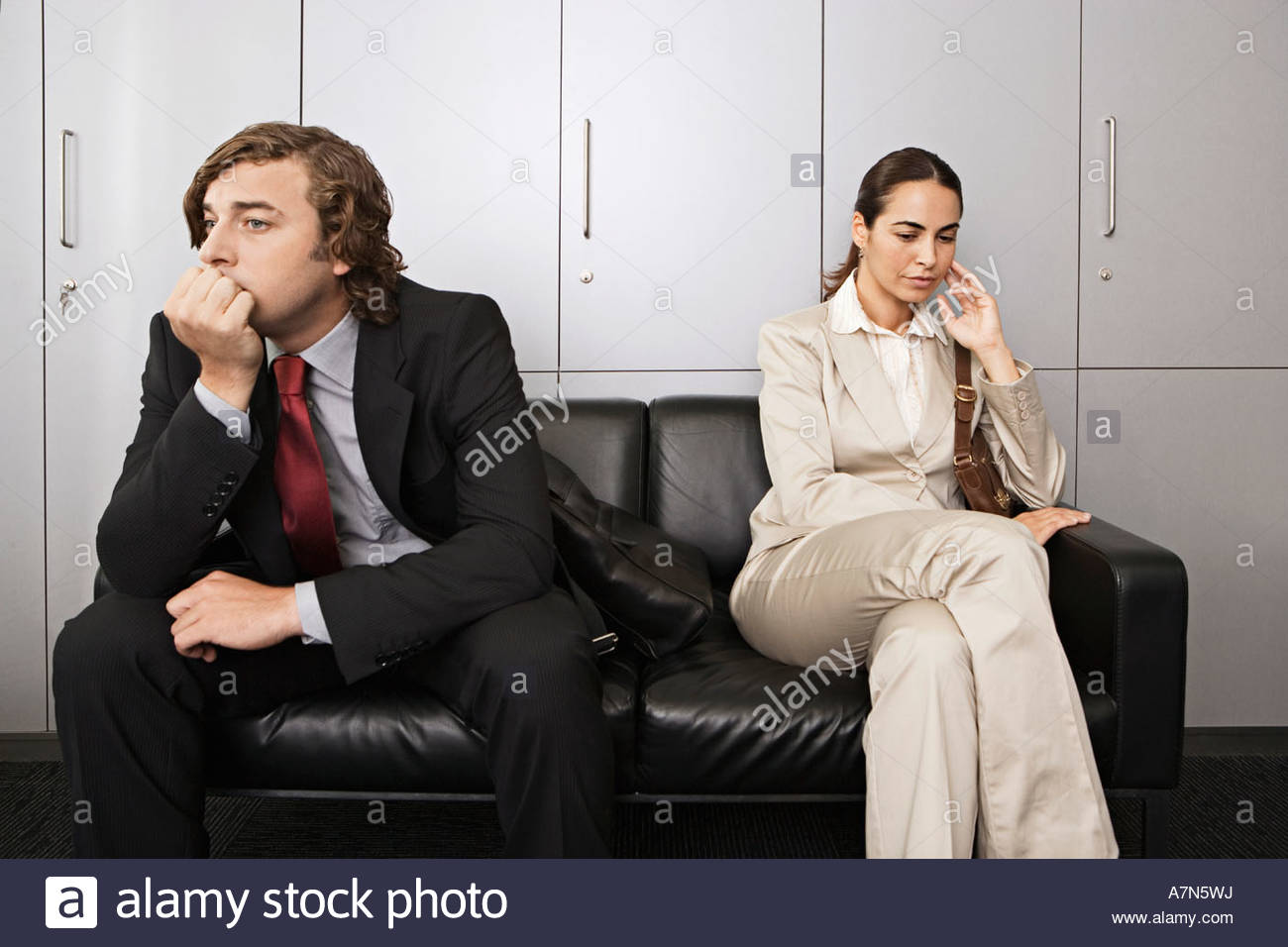 Anxious businessman and businesswoman sitting on sofa in office reception area waiting patiently - Stock Image