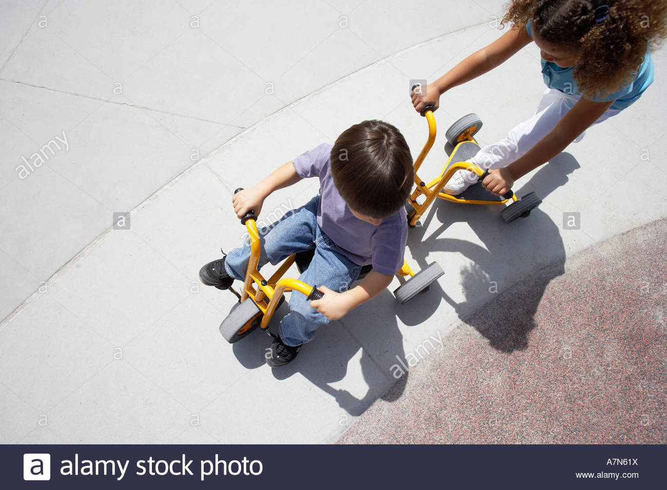 Boy and girl 4 6 riding toy tricycle and push scooter in playground overhead view - Stock Image