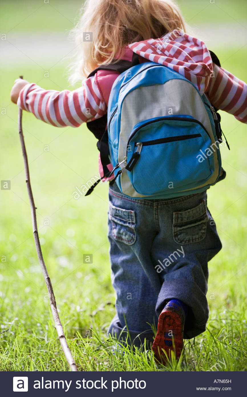 df6628bf88bb Girl 4 6 hiking on grass carrying rucksack holding stick rear view ...