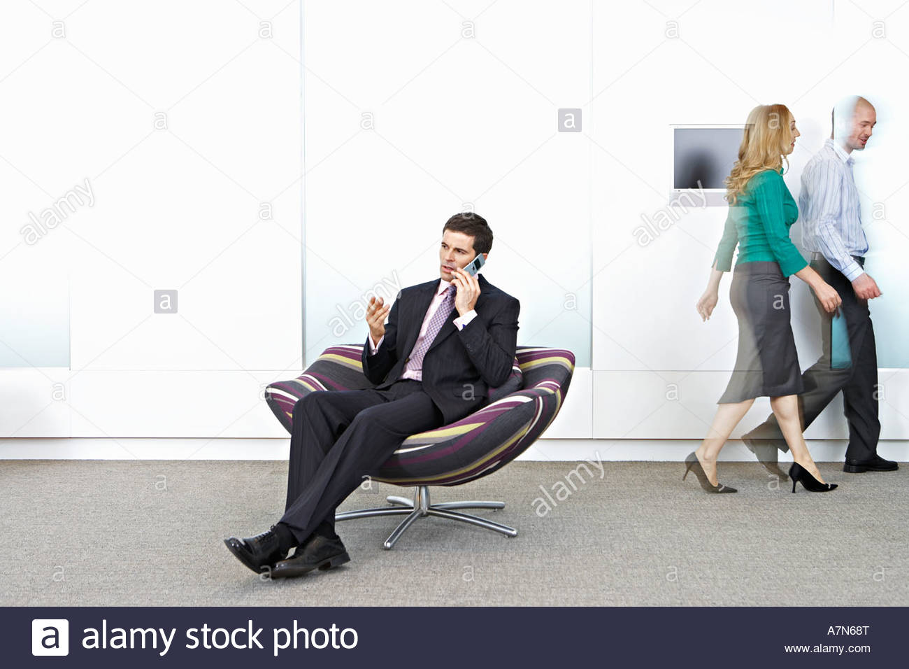 Businessman sitting in chair in office lobby using mobile phone colleagues walking in background - Stock Image